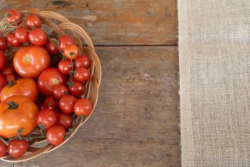 Vários tipos de tomate vermelhos, disposto em vasilha rústica, com área para escrita.