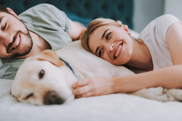Positive smiling couple resting with their dog while lying in bed