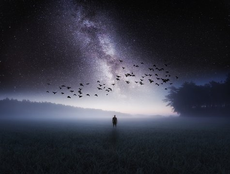Dreamy surreal landscape with starry night sky and man silhouette