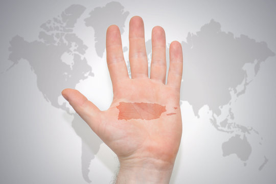 hand with map of puerto rico on the gray world map background.