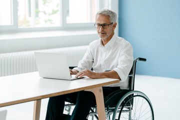 Handicapped manager in a wheelchair, working in office