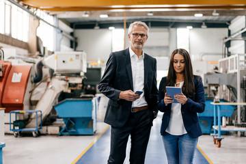 Businessman an woman in high tech enterprise, having a meeting in factory workshop