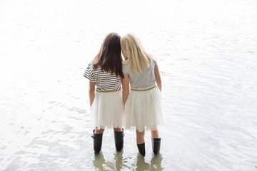 Back view of two best friends standing head to head in a lake