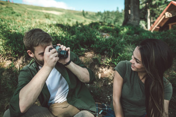 Catch the moments of journey. Waist up portrait of young guy photographing his smiling girlfriend on green mountain hill
