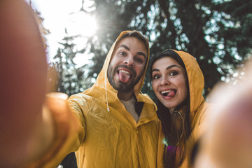 Enjoying journey in any weather. Close up portrait of happy man and woman in raincoats making funny selfie on green trees background