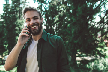 Communication during interesting travelling. Close up portrait of young cheerful man talking by...
