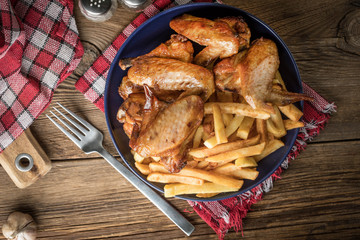 Baked chicken wings with french fries.