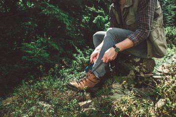 Take a break in journey and adventure. Close up side on portrait of young man sitting on stone of green hill to fasten shoe-laces