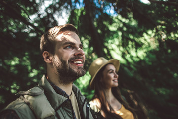 Concept of enjoying journey and adventure. Close up portrait of happy man and woman standing in sunny green leafs of forest