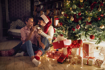 couple opening presents by Christmas tree