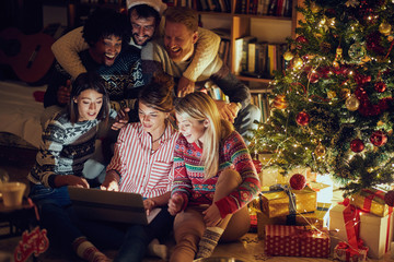 friends watching laptop by Christmas tree
