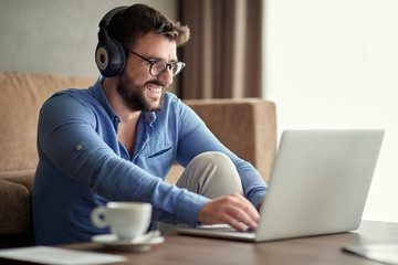 Smiling man with headphones using laptop in his home.