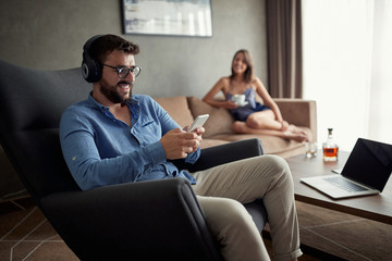 man uses a phone to listen to music and relax at home.