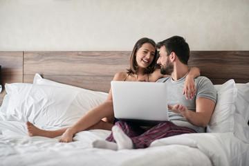 Happy couple lying on a bed with computer -  People, sexual, technology concept.
