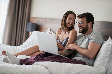 Man and woman watching video on laptop and laughing together.