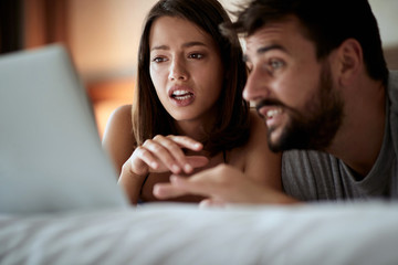 man and woman relax in bed with laptop lying together.