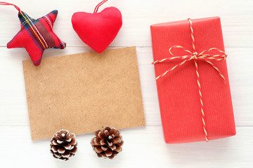 Red vintage gift box, blank brown paper greeting card and ornament on white wood background with copy space, Christmas, new year, valentine's day and anniversary greeting card background