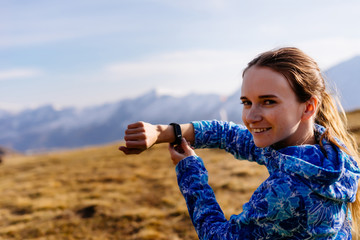 beautiful young traveler in a blue jacket shows time on a wristwatch, smiles against the background of the Caucasian mountains