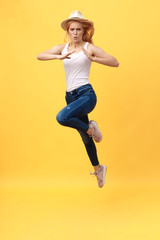 Young woman jump karate kicking in mid air isolated over yellow summer background