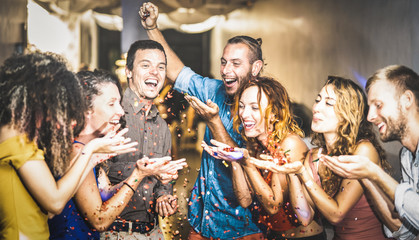 Multiracial happy friend having fun at new year's eve celebration - Young people blowing confetti at after party in night club - Friendship concept on cool entertainment mood - Focus on blue shirt guy