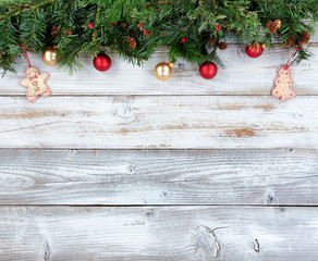 Top border of Christmas evergreen branches with other holiday decorations on white rustic wooden boards
