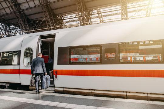 Geschäftsmann im Anzug steigt in Zug ein