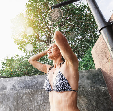 Young beautiful happy smiling woman taking a shower outdoors, after the pool in the sun