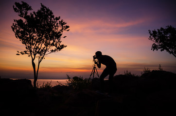 Silhouette Young man photographer taking nature photo on PhraYa Dern Thong mountain landscape.province Lopburi.Thailand. tourist photographe shooting dslr camera on tripod