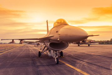 fighter jet military aircraft parked on runway standby ready to take off on sunset Wall mural