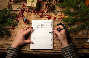 Woman writing her New Year resolutions