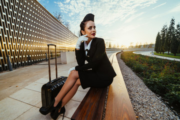 young confident woman stewardess in uniform sits in the park and waits for her flight, with a suitcase