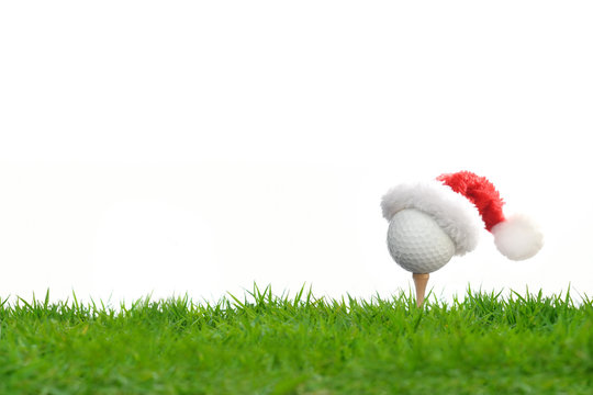 Festive-looking golf ball on tee with Santa Claus' hat on top for holiday season isolated on white background