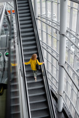 A ginger white girl on an escalator. A smiling girl with curly hair. Bright yellow sweater.