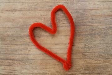 Red heart pipe cleaner on wood background
