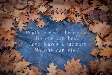 "Dried, browned oak leaves on a background of blue/gray granite with text in the middle reading ""Death leaves a heartache, no one can heal, love leaves a memory no one can steal"""