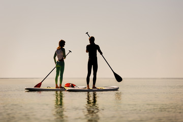 Silhouette of young happy couple doing paddle yoga