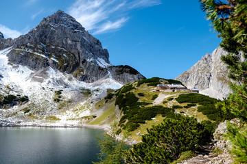 Gebirgslandschaft mit See und Hütte