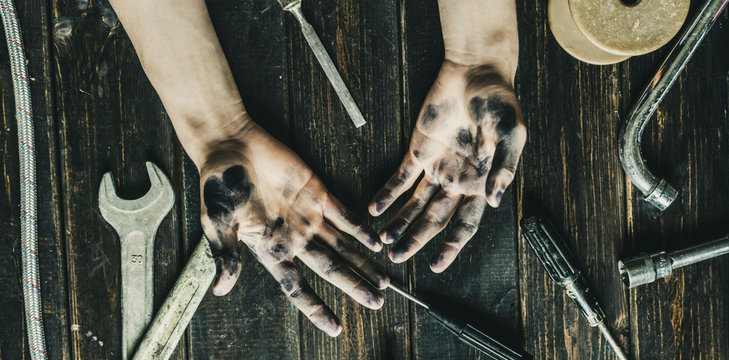 worker class person dirty dark hands on the wooden table with tools equipment f