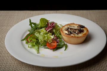julienne in tartlet with salad and tomatoes on a white plate