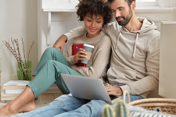 Relationship and technology concept. Relaxed couple embrace, look at laptop, check news feed in social networks, buy something online, spend weekend at home, pose on floor, satisfied with free wifi