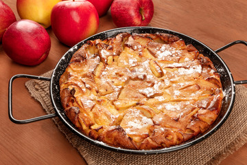 A photo of an apple pie in a pan, on a dark rustic wooden background with heirloom apples