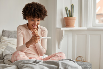 Photo of glad smiling ethnic woman looks happily at positive pregnancy test result, cant believe she will become mother, sits at bed, feels pleased, enjoys recreation time, anticipates for baby