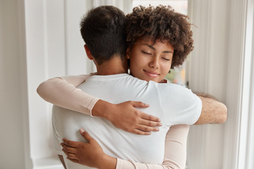Back view of Caucasian guy embraces her girlfriend, stand closely to each other, express love and support, comfort, express empathy, have good relations. People, care and relationship concept