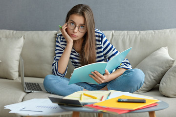 Photo of attractive woman writes article, develops startup project, enjoys comfort, poses in living room on sofa with laptop computer, sits crossed legs, wears round optical glasses, has serious look