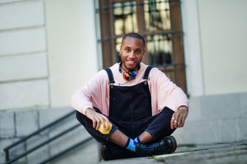 Young black man eating an apple sitting on urban steps.