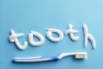 """Word """"tooth"""" written with white toothpaste. Toothpaste text and blue toothbrushe on blue. White toothpaste letters on blue. Clean on blue. Clean teeth."""