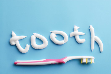 """Word """"tooth"""" written with white toothpaste. Toothpaste text and pink toothbrushe on blue. White toothpaste letters on blue. Clean on blue. Clean teeth."""