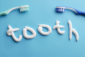"""Word """"tooth"""" written with white toothpaste. Toothpaste text and toothbrushes on blue. White toothpaste letters on blue. Clean on blue. Clean teeth."""