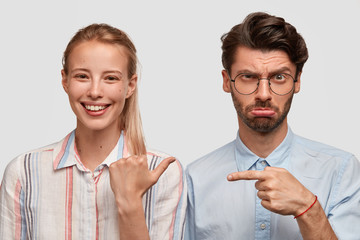 Wall Mural - Horizontal view of cheerful European young woman with pony tail, dressed in shirt, points at her dissatisfied husband who has some failure, model against white background. Relationship concept