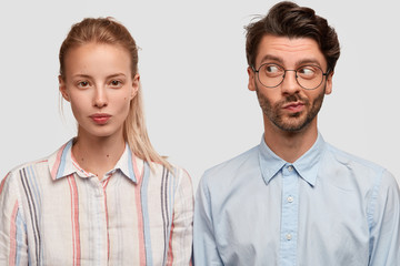 Indoor shot of friendly mixed race woman and man dressed in stylish shirts, pose together against white background, think about creative solution, collaborate for common task. Brother and sister